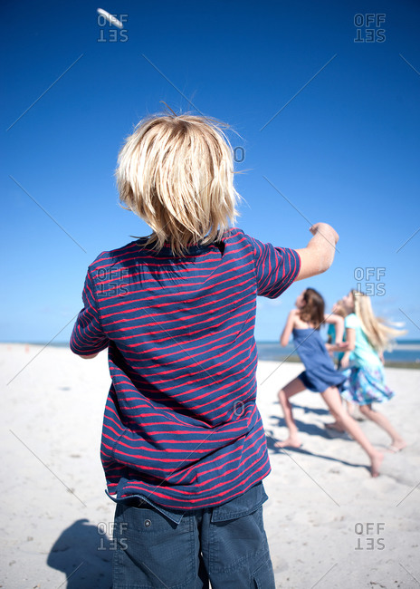 Children playing with a flying disc on a beach