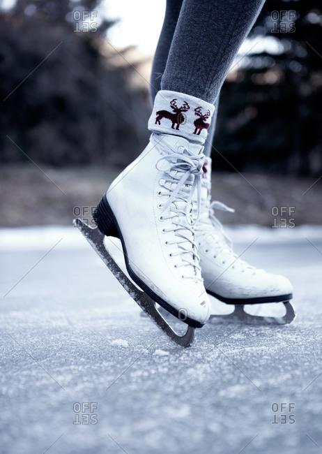 Woman wearing ice skates on a frozen lake
