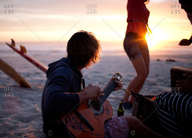 Man playing the guitar on a beach