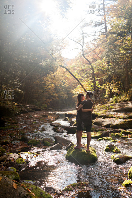 Romantic young couple embrace while standing on a rock in a stream