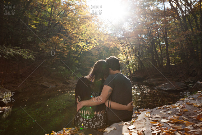 Romantic young couple seated with arms around each other on a rock above a stream