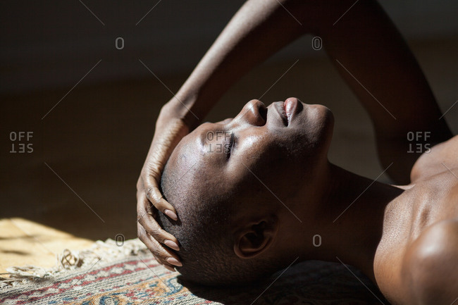 Woman lying on floor with her hand on her head in sunlight