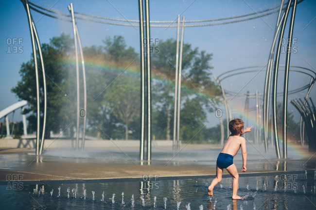 Little boy running through city fountain