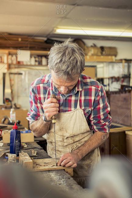 Furniture restorer working with handheld tool