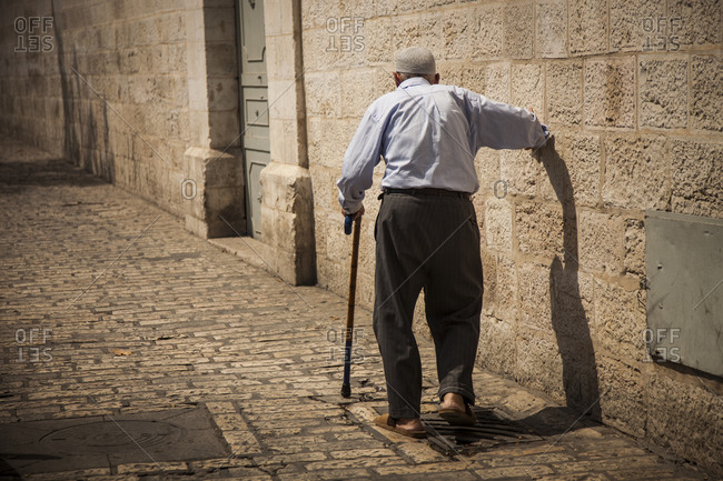 An old man walks down the street in the Arab Quarter of Jerusalem