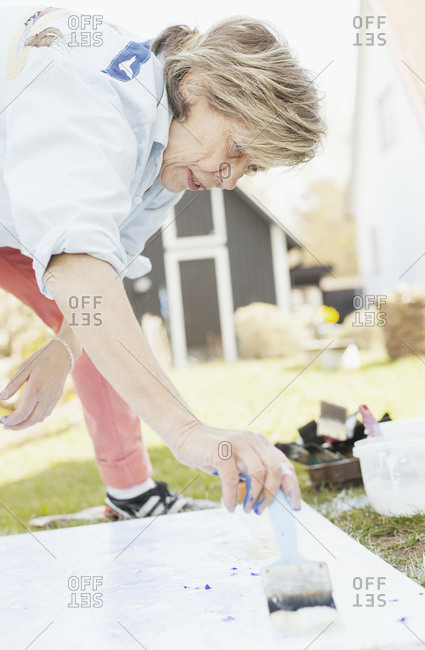Senior female artist painting outdoors