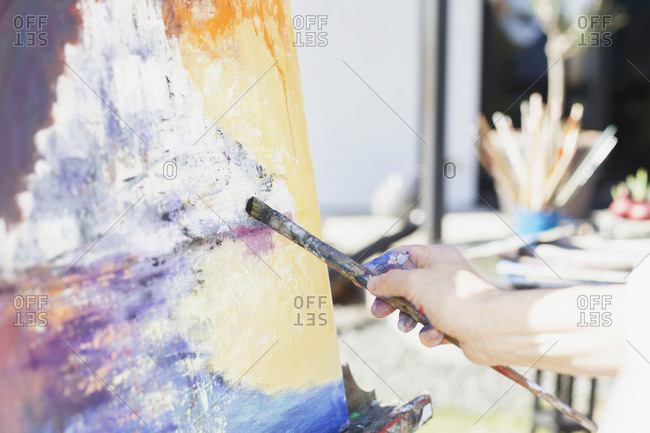 Close up of an artist's brush and painting outdoors