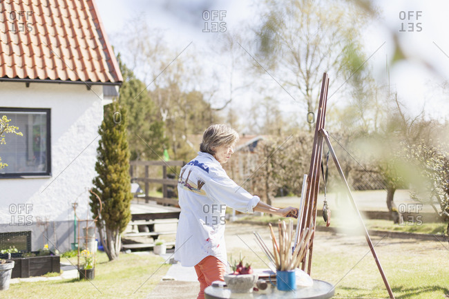 Senior female artist using an easel to paint outdoors