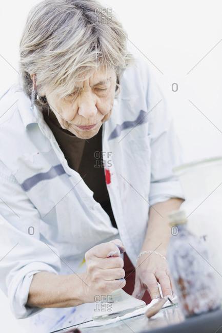 Senior female artist mixing paint