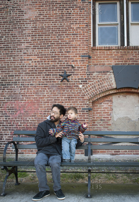 Father and young son on a park bench