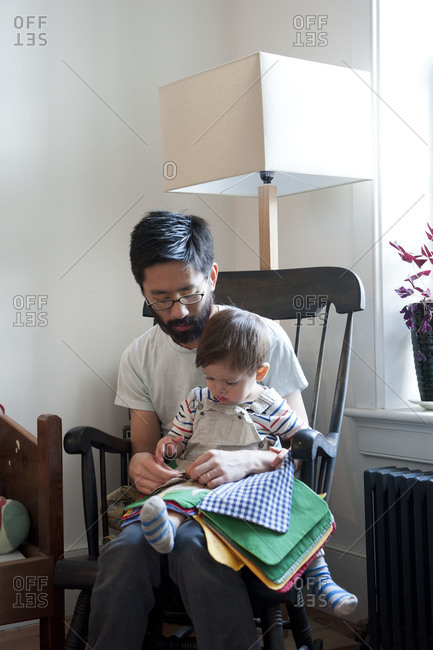Father reads a book to his young son