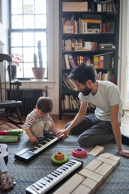 Father teaching his young son to play keyboard
