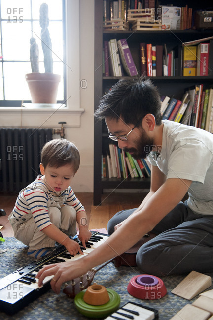 Father teaching young boy to play keyboard