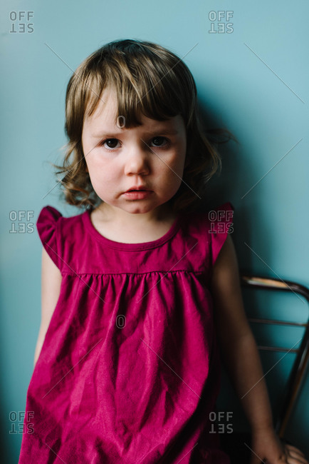 A little girl in a purple shirt stands against a blue wall