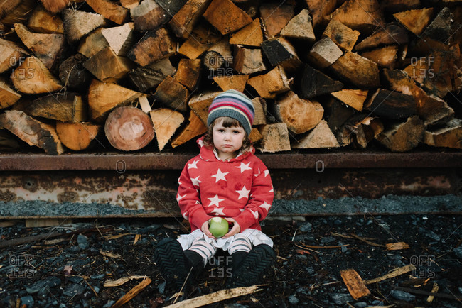 A girl sits by a woodpile looking upset