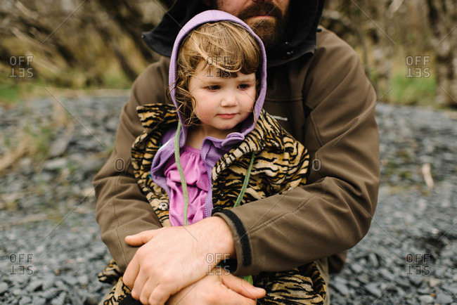 A father hugs his daughter outside on a gray day