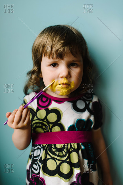 A little girl paints her face yellow