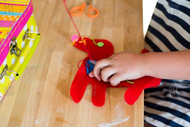 A little girl sews a felt puppy
