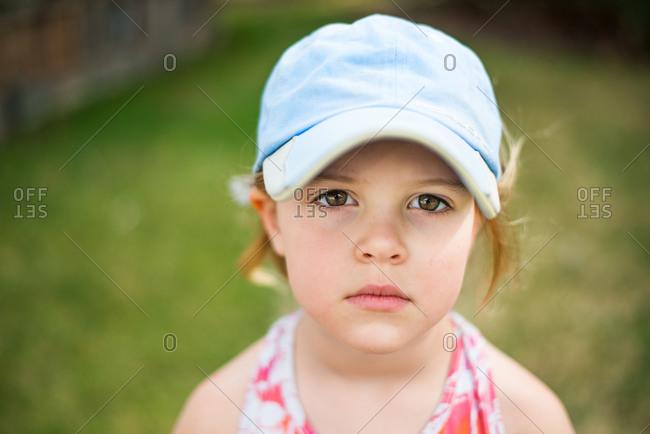 A little girl stands glumly outside