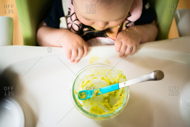 A baby stares at its bowl of food