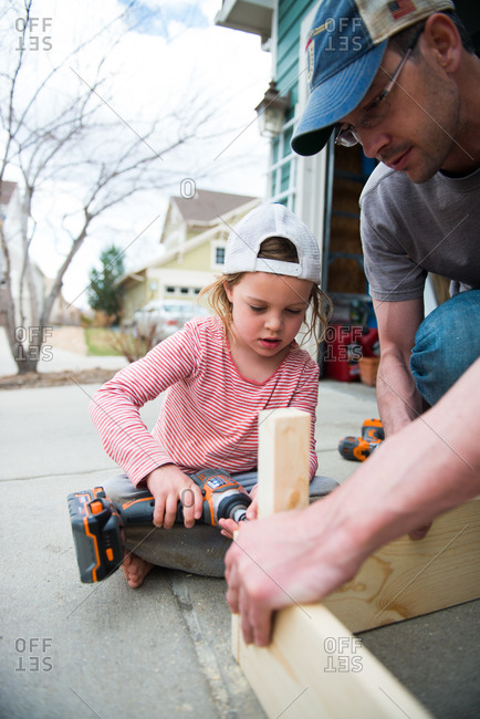Father teaching his daughter to use a power drill