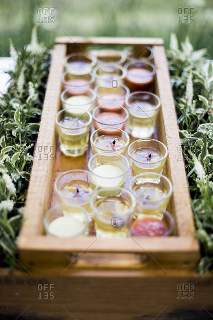 Chilled soups in shot glasses served in a wooden box surrounded by herbs