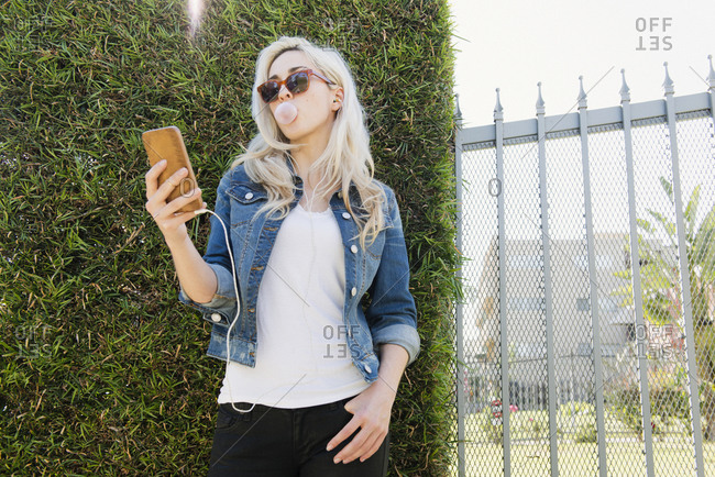 Blonde woman using her smartphone while blowing a bubble