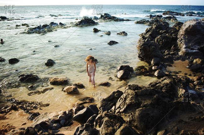 Woman wading in the water on a rocky coast