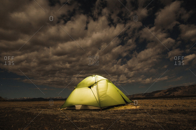 Green tent lit from within in an open field at night