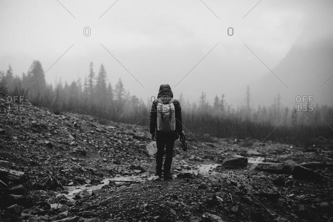 Hiker near a small stream in a rocky gray landscape