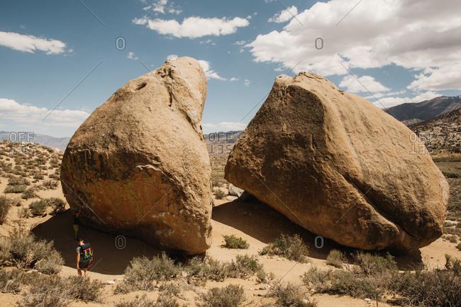 Hiker walks past a giant boulder that has been split in two in the desert