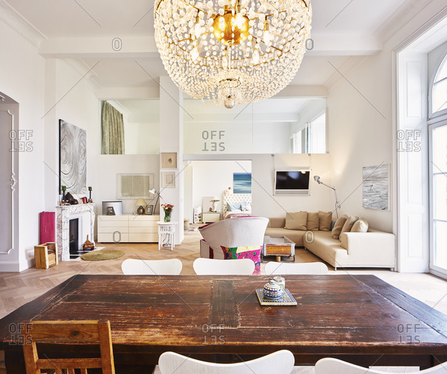 Living room in a refurbished old building with dining table in the foreground