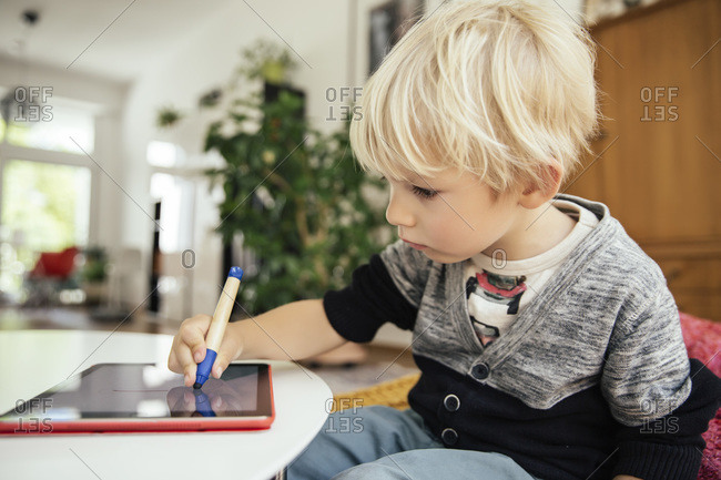 Little boy drawing with a digital pen on digital tablet at home