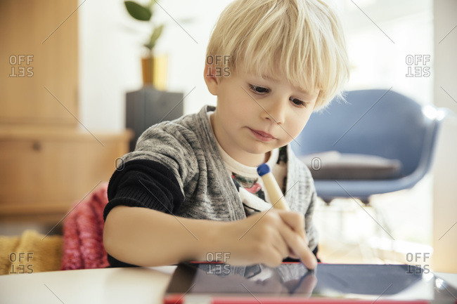 Portrait of little boy drawing with a digital pen on digital tablet at home