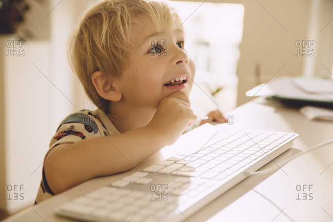 Smiling little boy looking at the screen of a computer