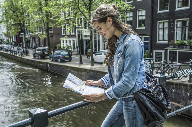 Female tourist looking at city map in front of town canal, Amsterdam
