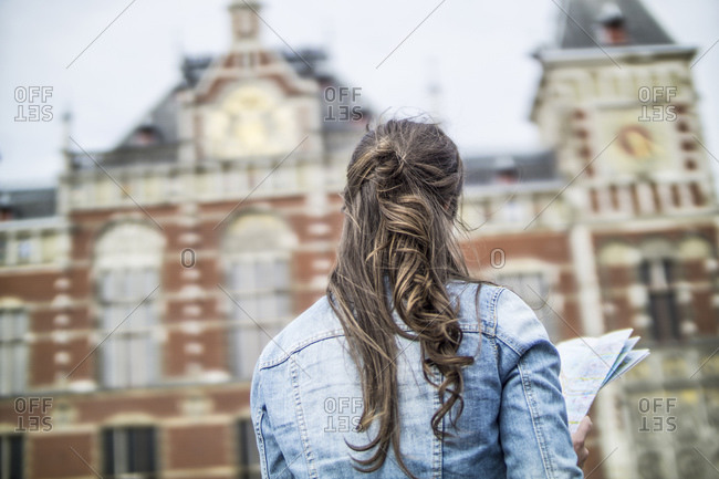 Back view of woman with city map in front of central station, Amsterdam