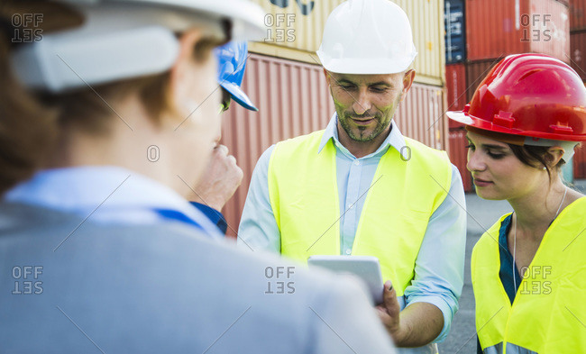 Four people with safety helmets and digital tablet talking at container port