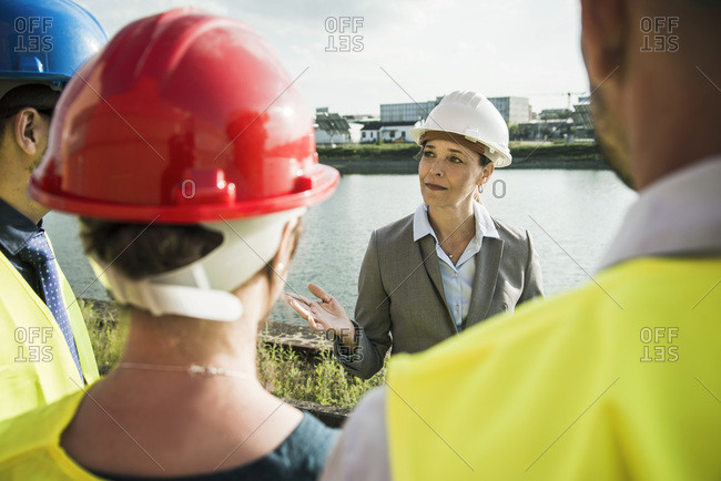Businesswoman talking to people with safety helmets at riverside