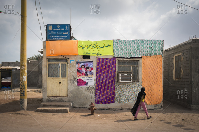 Hormuz Island, Iran - February 9, 2015: A girl walks past a colorfully adorned house with images of past and present leaders in a small community in the Persian Gulf.