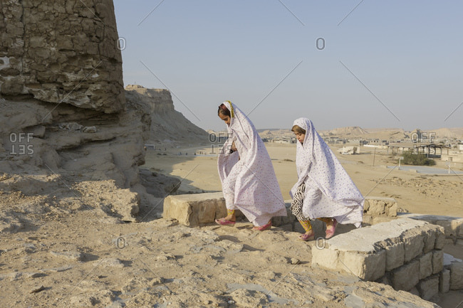 Qeshm Island, Iran - February 7, 2015: Two young girls pass the ruins of a Portuguese castle in the village of Laft on Qeshm Island in the Persian Gulf