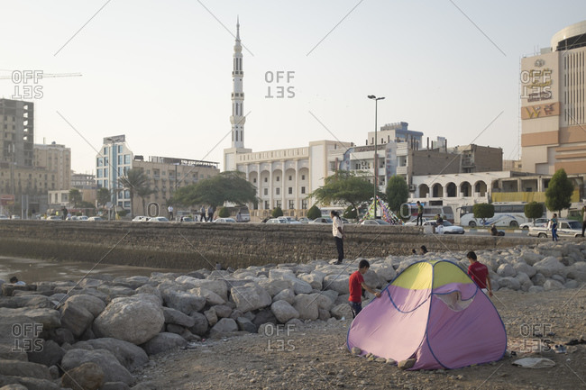 Bandar Abbas, Iran - February 6, 2015: A young family spends the afternoon on the foreshore of the Persian Gulf coast port city of Bandar Abbas