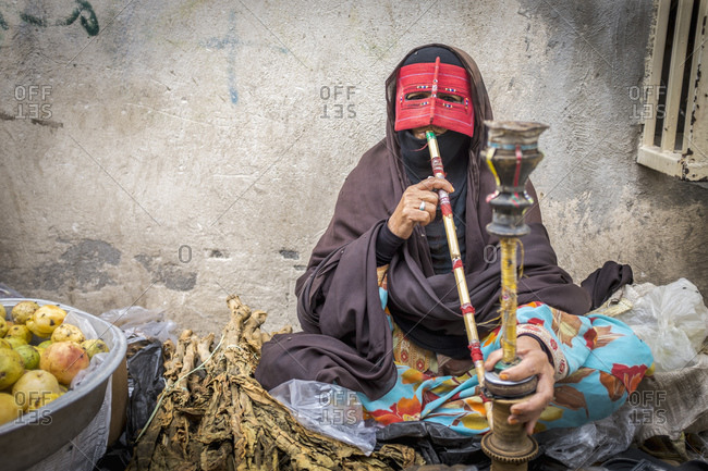 Minab, Iran - February 5, 2015: A female vendor smoking tobacco from a water pipe or 'nargeela,' a practice that is banned for women throughout Iran in public places, but remains popular amongst the vendors at the weekly Panjshambe Bazar
