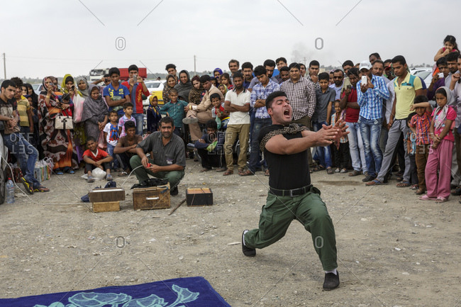 Minab, Iran - February 5, 2015: A strongman theatrically struggles to break free of chains at the Thursday market or Panjshambe Bazar