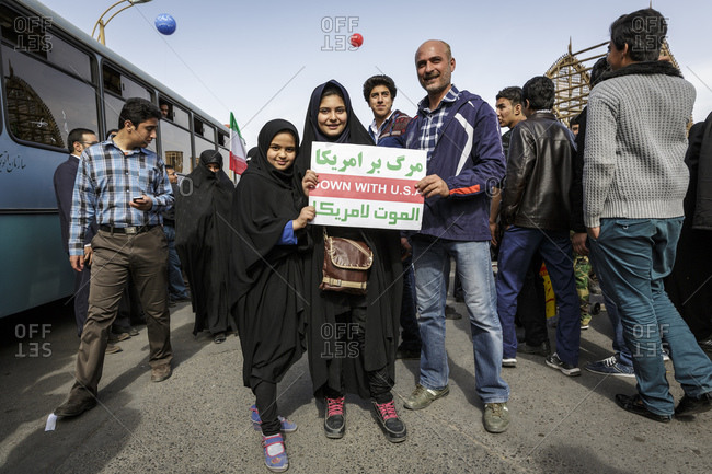 Yazd, Iran - February 11, 2015: Family at the mass rallies during the 'Ten Days of Dawn', the 36th anniversary of the Islamic Revolution