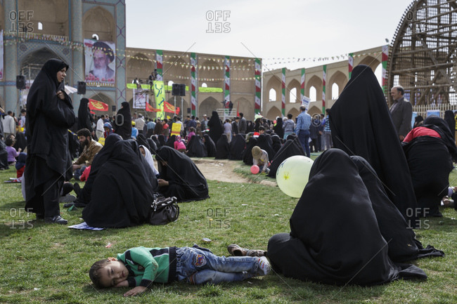 Yazd, Iran - February 11, 2015: A very tired young boy and crowds dispersing after lengthy speeches by officials at the 'Ten Days of Dawn' protests