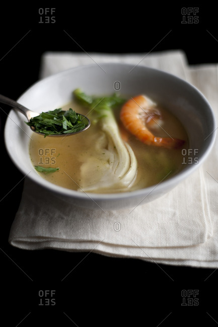 Clear broth soup with shrimp, herbs, and bok choy