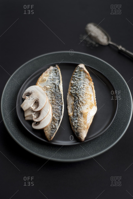 Two pieces of cooked fish with sliced mushrooms on black plate