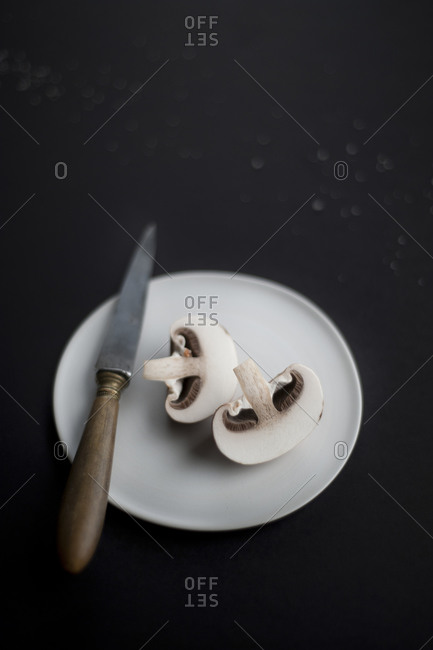 Fresh mushroom sliced in half on white plate with knife on black background