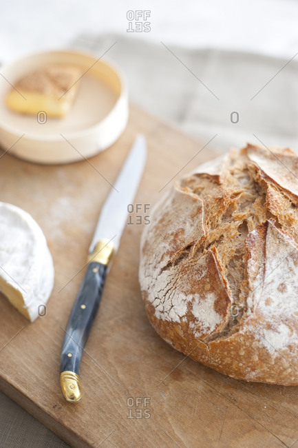 Wooden cutting board with loaf of bread, knife and cheeses